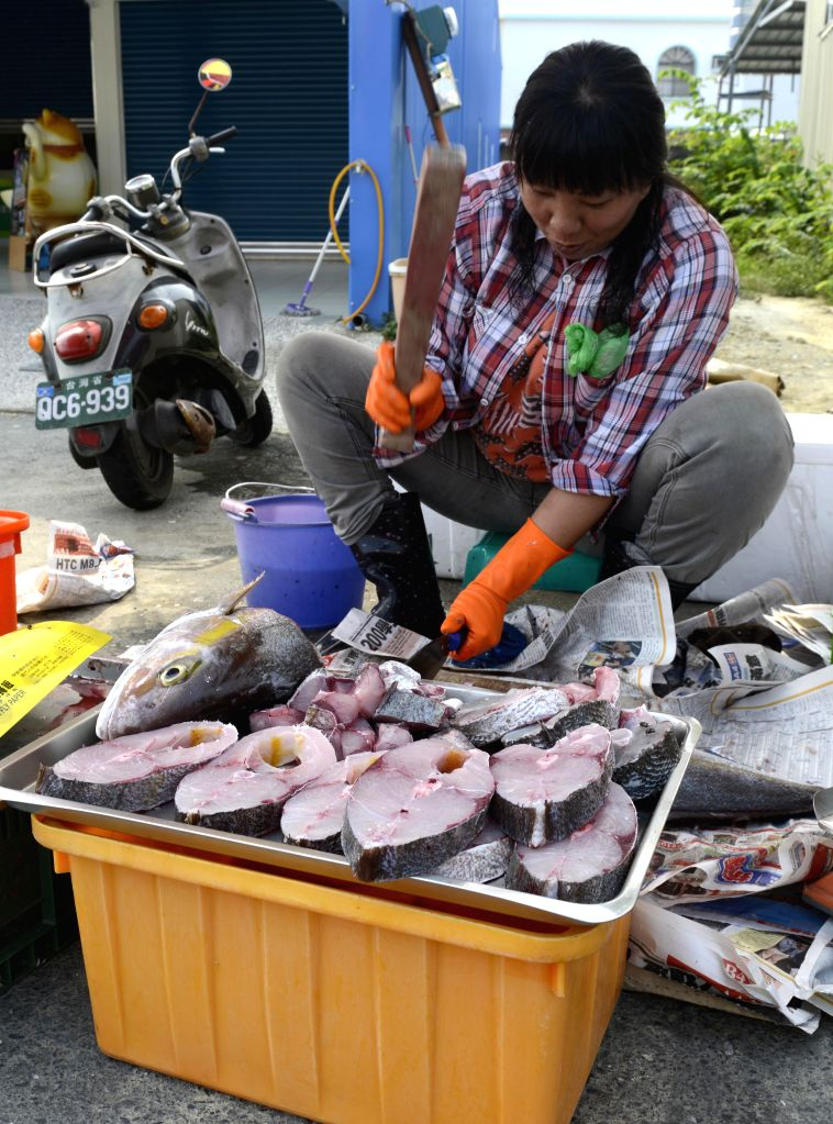 A woman sells fishes on a street in Liouciou Township in Pingtung County, southeast China's Taiwan, April 21, 2014. Liouciou township, which locates 8-9 nautical .