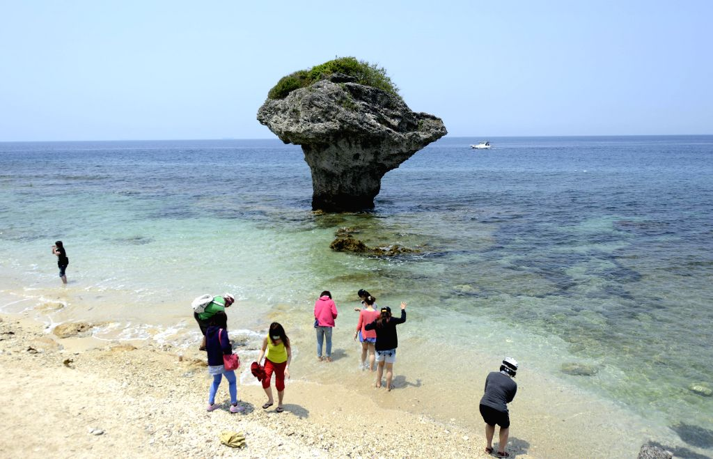 Tourists frolic beside vase rock, a landmark in Liouciou Township in Pingtung County, southeast China's Taiwan, April 21, 2014. Liouciou township, which locates ..