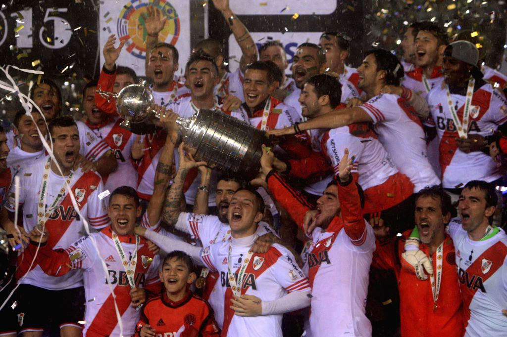 Players of Argentina's River Plate celebrate with the trophy at the end of the second final match of Copa Liberators against Tigers of Mexico, at Monumental ...