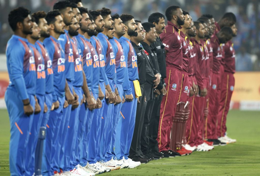 Players of India and West Indies stand for National Anthem ahead of the first T20I match between India and the West Indies at the Rajiv Gandhi International Stadium in Hyderabad on Dec 6, ...