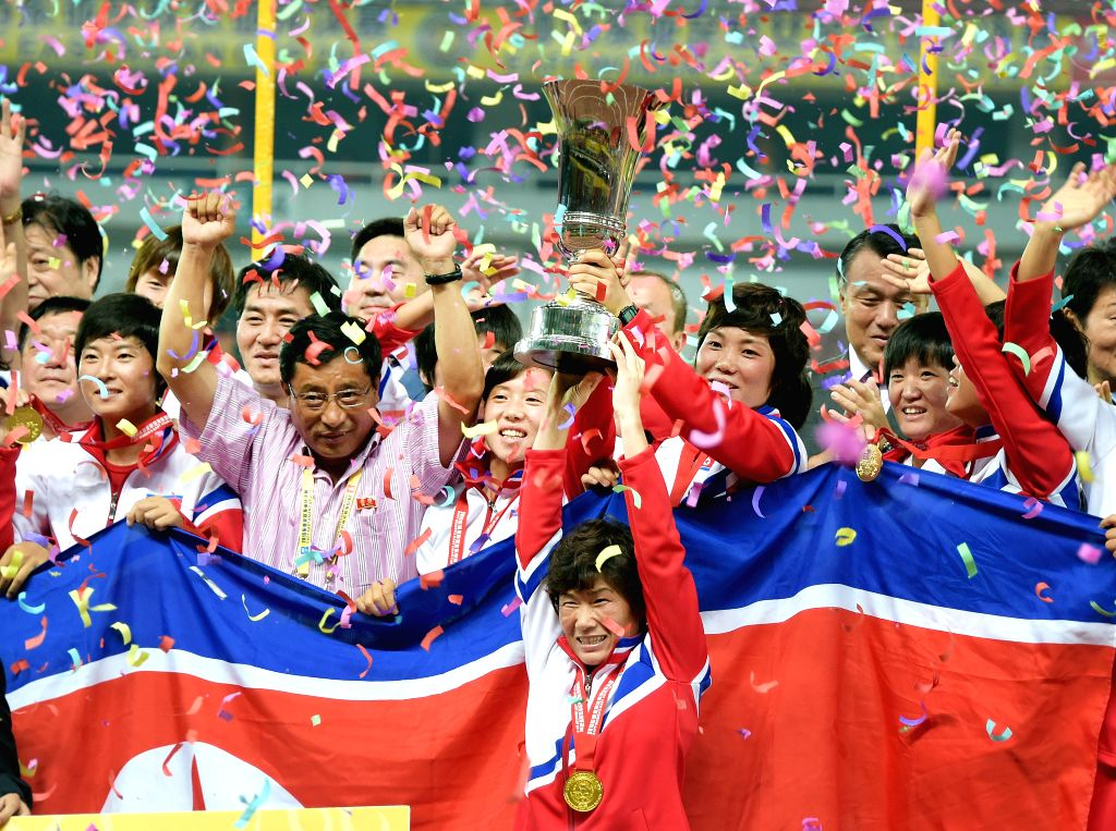 Players of the Democratic People's Republic of Korea (DPRK) celebrate with the trophy at the awarding ceremony after the match against South Korea at the 2015 ...