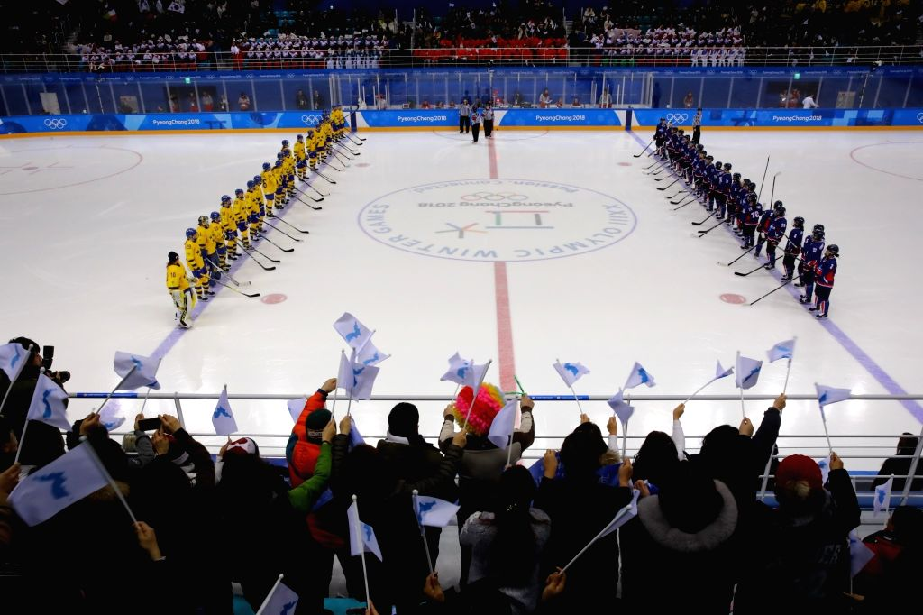 Players of the unified Korean team and the Swedish squad line up for a women's preliminary round ice hockey game at the PyeongChang Winter Olympics at the Kwandong Hockey Centre in ...