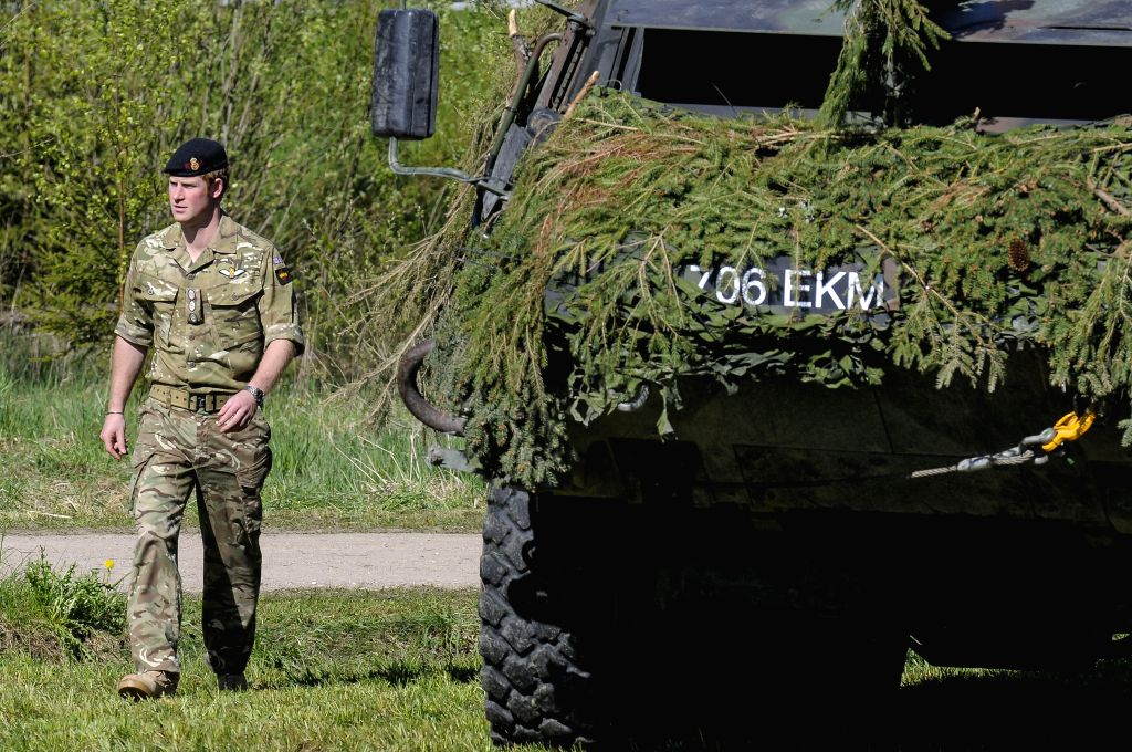 Britain's Prince Harry walks beside a armored vehicle on May 17, 2014 during a visit to the Estonian Defence Forces annual pring Stormtraining exercises held near ..