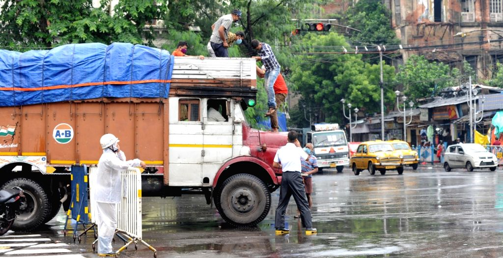 Police are getting down the worker who climbed on the lorry illegally in the rain in Kolkata on Saturday, 19 June, 2021.