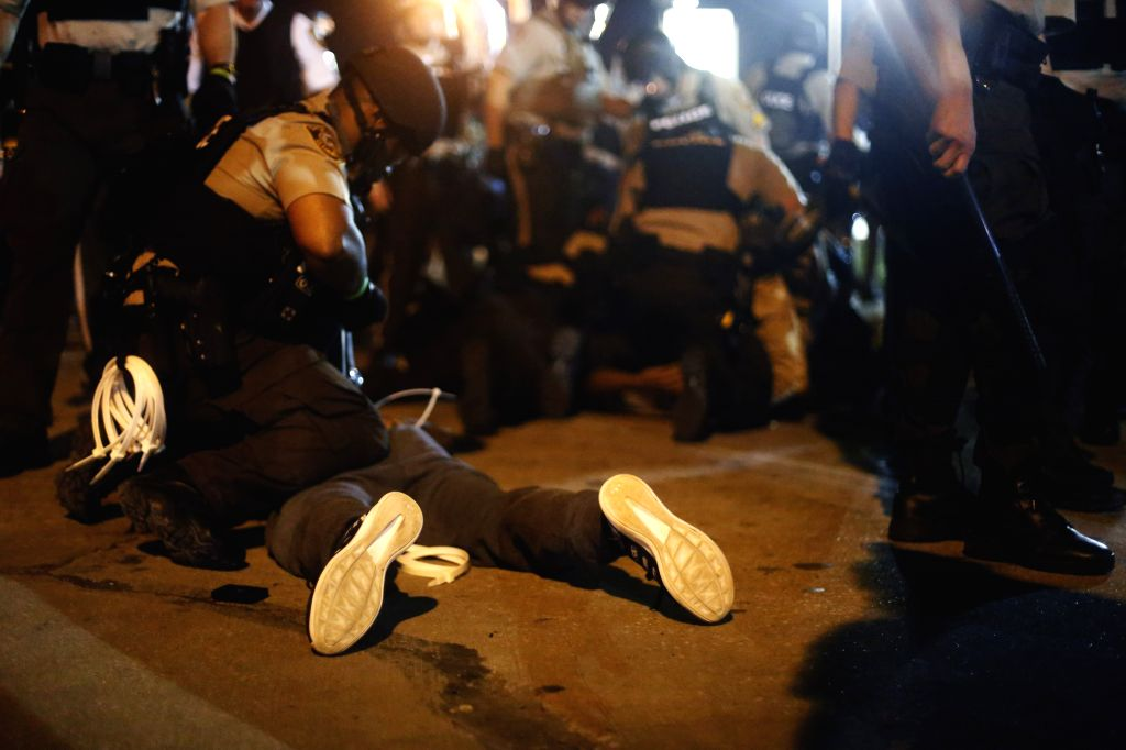 Police arrest protesters in the street in Ferguson, Missouri, the United States, on August 10, 2015. A state of emergency has been declared for the city of ...