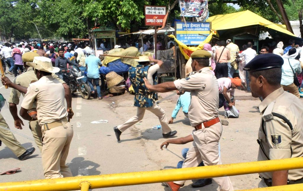 Police charge baton on teachers staging a protest in Patna on July 18, 2019.