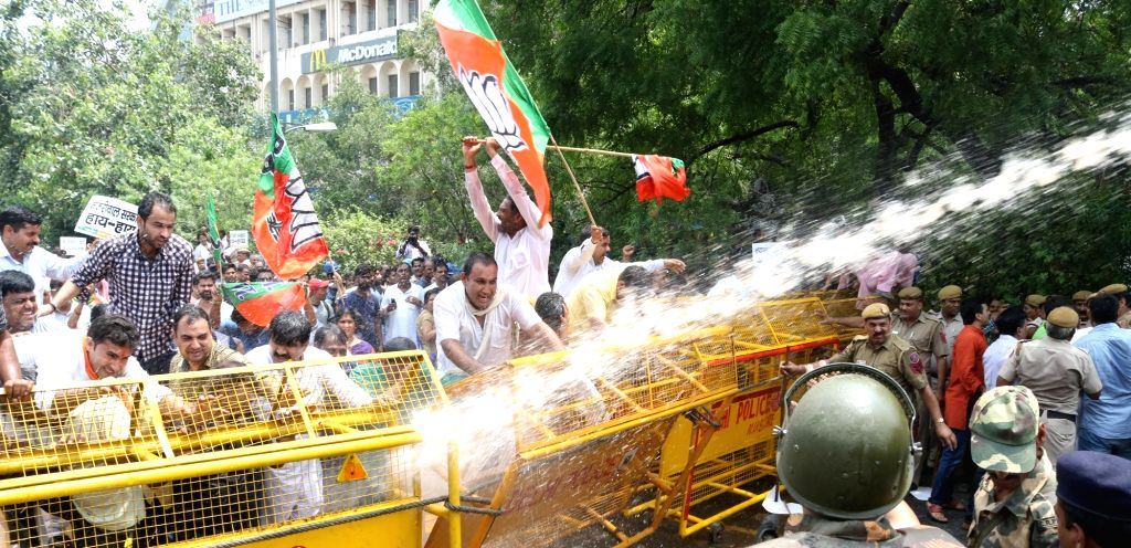 Police charge water cannons on BJP workers demonstrating against Chief Minister Arvind Kejriwal in New Delhi on July 6, 2016. - Arvind Kejriwal