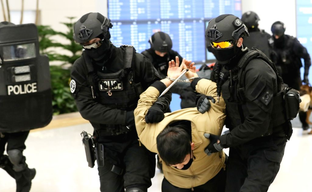Police commandos overpower a simulated terrorist at the second terminal of Incheon airport, west of Seoul, on Jan. 31, 2018, as they stage a drill involving a staged scenario of terrorists ...