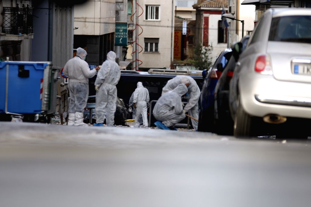 Police forensic experts search for evidence at the site of an explosion in central Athens, Greece, on Nov. 24, 2015. A bomb attack occurred outside the offices of ...