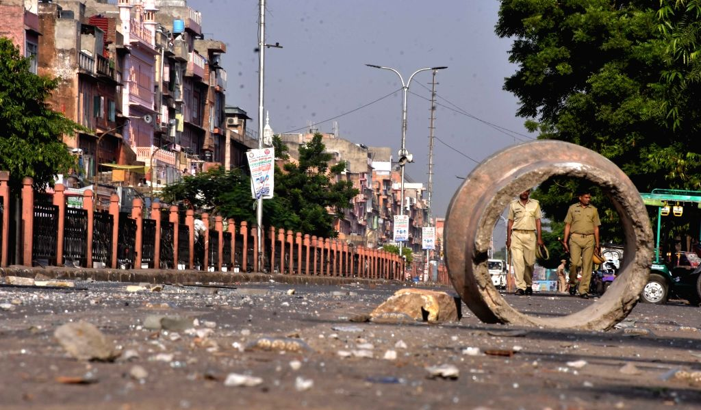 Police guards the streets as curfew was imposed following violence that erupted between locals and the police after a policeman hit a person sitting on a motor bike with a baton in Jaipur on ...