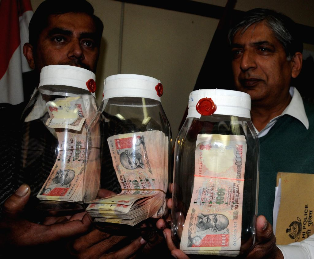 Police officers display fake Indian currency notes with face value of Rs 4.5 Lakhs seized from three persons in New Delhi on Jan.12, 2014. (Photo: IANS)
