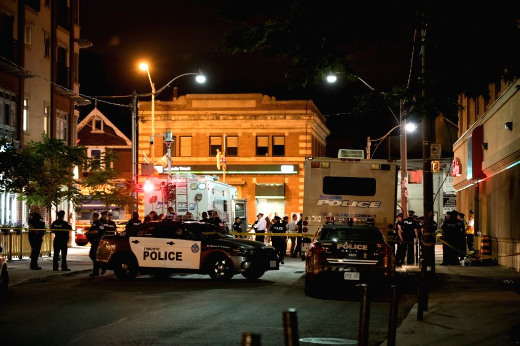 :Police officers gather at the crime scene in Toronto, Canada, on July 23, 2018. A man shot 14 people, killing one and injuring 13 others in Toronto's ...