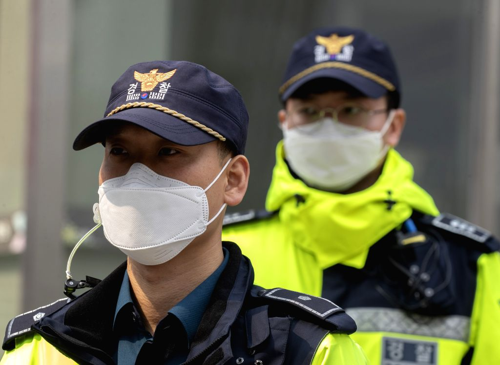 Police officers maintain order at the gate of a sanatorium where mass coronavirus infections occurred in Daegu, South Korea, March 19, 2020. South Korea reported 152 ...