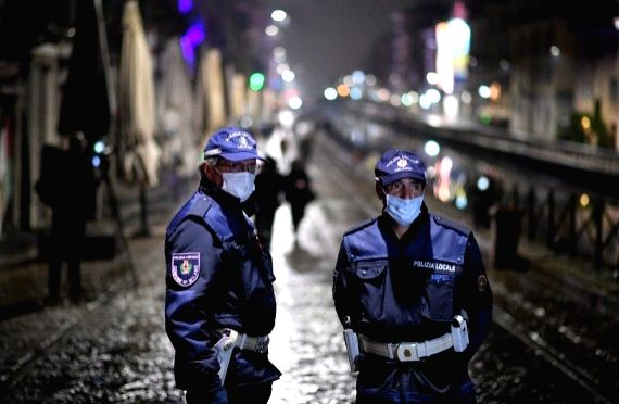 Police officers patrol a street amid a spike in new coronavirus infections in Milan, Italy, Oct. 22, 2020.
