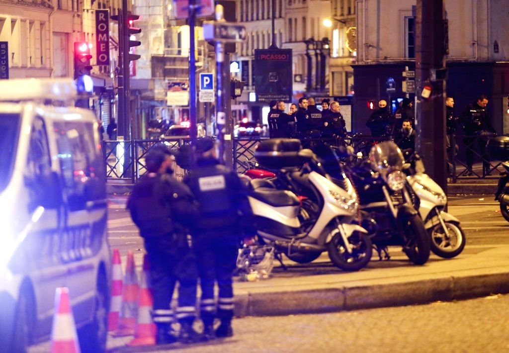 :Police officers stand guard at a road leading to the Bataclan concert hall in Paris Nov. 14, 2015. Over 100 people were killed in a mass hostage-taking at the ...