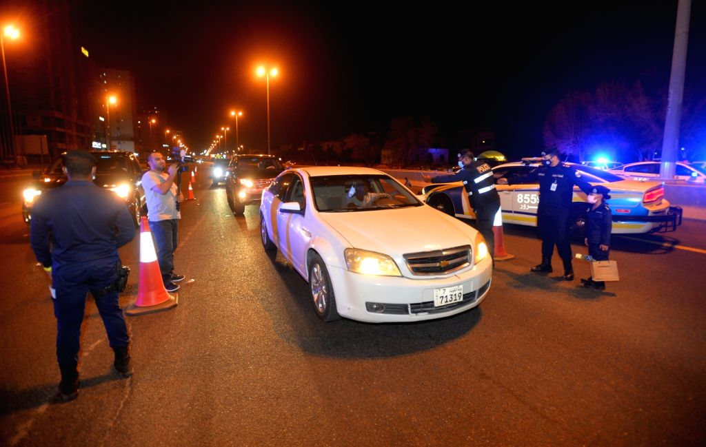 Police officers work at a checkpoint during a partial curfew imposed to stem the COVID-19 spread in Hawalli Governorate, Kuwait, Aug. 28, 2020. Kuwait ...
