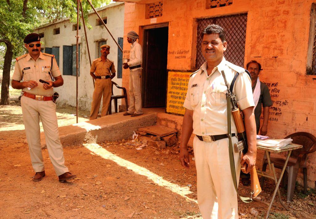 Police personals stands on guard at a polling booth as 2014 Lok Sabha polls at Karai village in Guna, Madhya Pradesh on April 17, 2014.