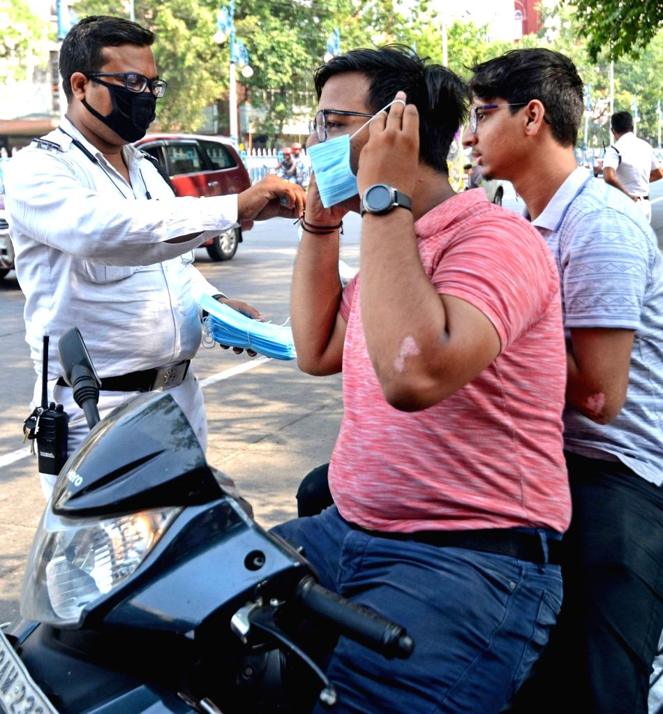 Police personnel are distributing masks to people without masks during the increasing numbers of COVID 19 patients in Kolkata. .