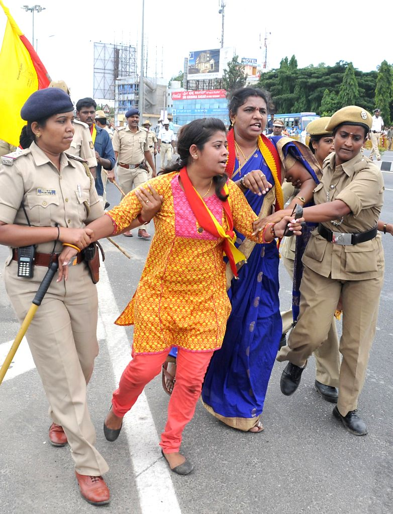 Police personnel arrest people protesting against hike in toll at Kempegowda International Airport in Bangalore on May 6, 2014.