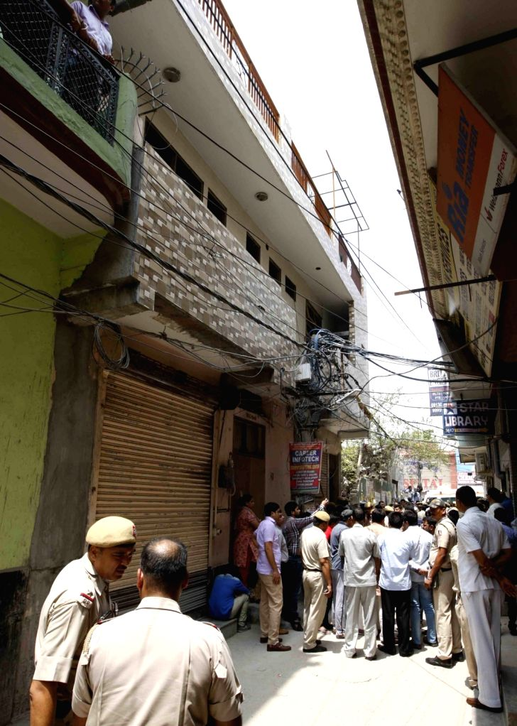 Police personnel at the site where 11 members of a family were found deadsome blindfolded and hanging from an iron grill ceilingat their home, in New Delhi on July 1, 2018. ...