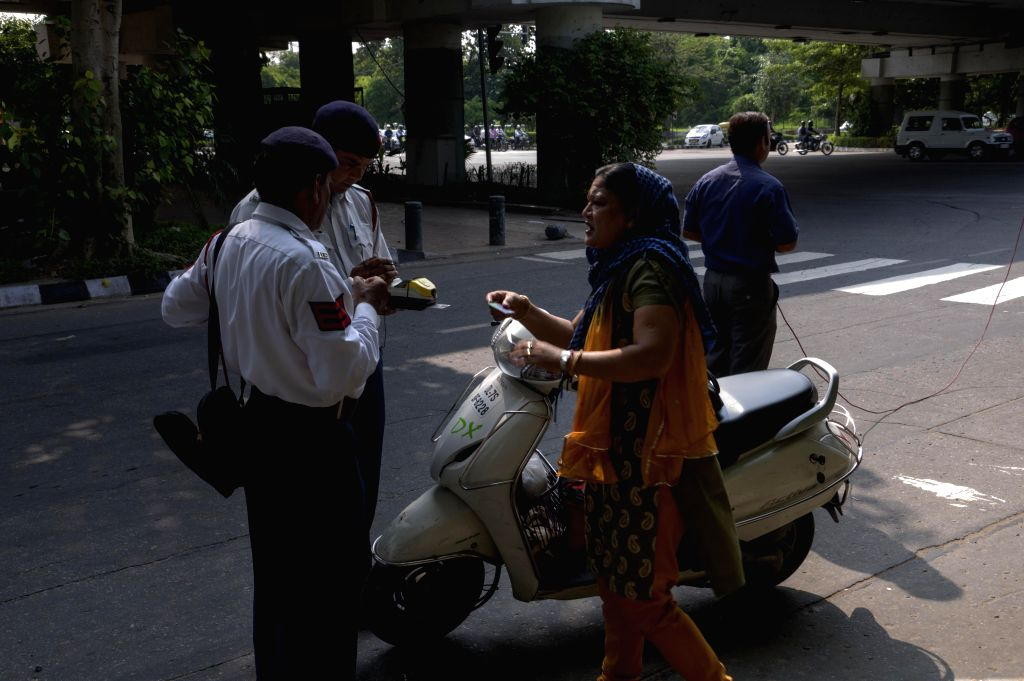 Police personnel book a scooterist for not wearing helmet in New Delhi on Sept 10, 2014. Last month the Delhi government has issued a notification making wearing of helmets mandatory for women.