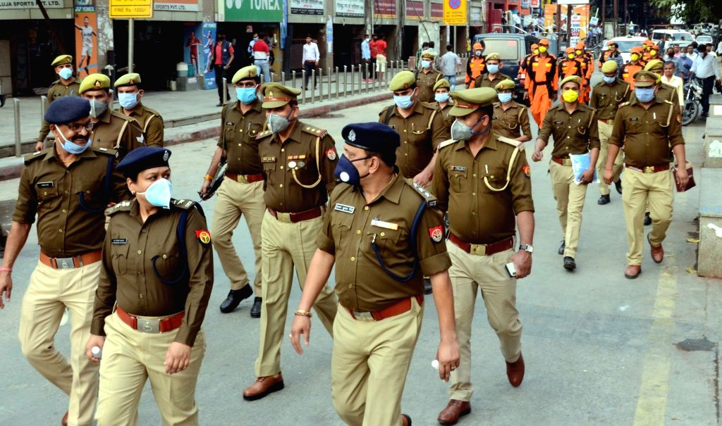 Police personnel conduct a flag march creating awareness among people on COVID-19 ahead of Sunday's nationwide 'Janata Curfew' imposed in the wake of increasing cases of coronavirus, in Noida ...