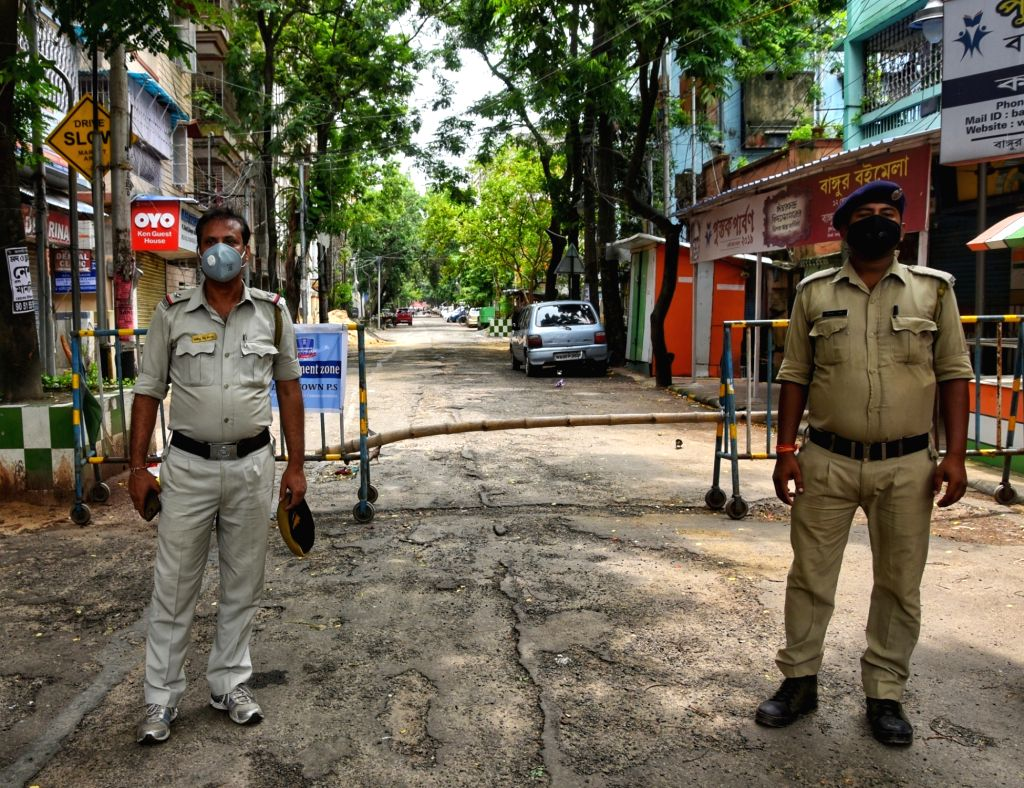 Police personnel deployed in a COVID-19 containment zone at Kolkata's Bangur Avenue Super market area during a complete lockdown imposed in all the designated containment zones across West ...