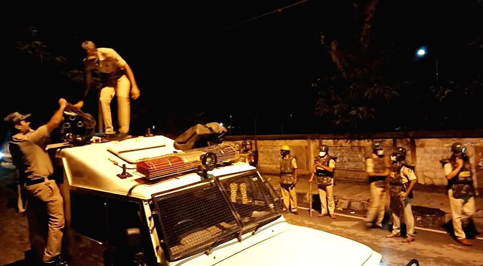 Police personnel deployed outside Congress legislator Akanda Srinivas Murthy's house where a mob gathered and shouted slogans over a derogatory post on social media, in Bengaluru on Aug ...