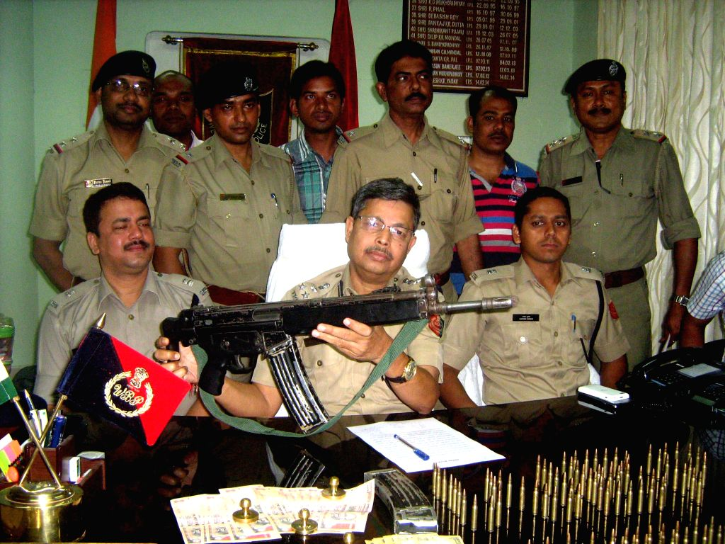 Police personnel display the automatic rifle and ammunition recovered from the suspected Kamtapur Liberation Organisation (KLO) leader Malkhan Singh, who was arrested from Jamalpur forest under ... - Malkhan Singh