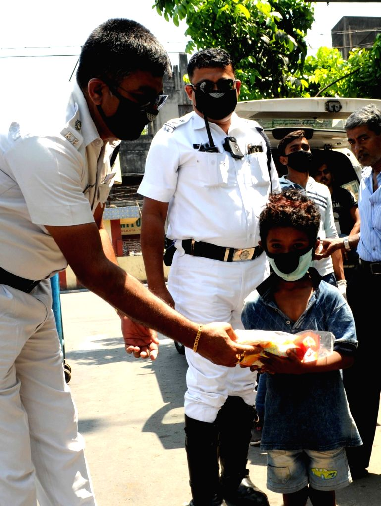 Police personnel distribute food among the poor, needy and homeless on Day 6 of the 21-day countrywide lockdown imposed to contain the spread of novel coronavirus, in Kolkata on March 30, ...