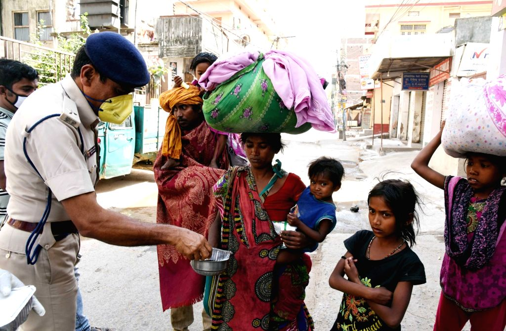 Police personnel distribute food among the poor and needy on Day 7 of the 21-day nationwide lockdown imposed as a measure to contain the spread of  coronavirus, in Patna on March 31, 2020.