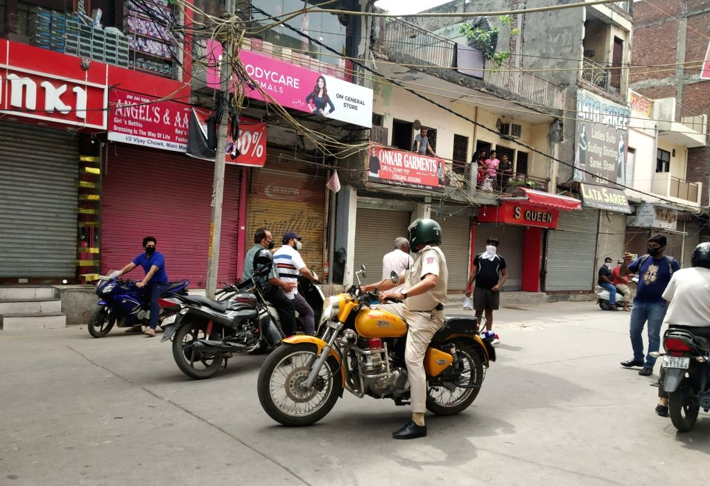 Police personnel ensure the proper implementation of lockdown as they instruct shopkeepers to close their stores opened without permission during the extended nationwide lockdown imposed ...