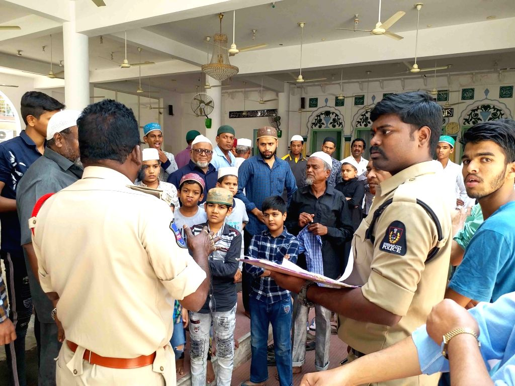 Police personnel interact with a group of Muslim devotees creating awareness among them on precautions to be taken to contain the spread of COVID-19 (coronavirus), in Hyderabad on March ...