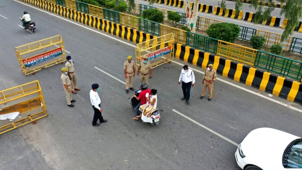 Police personnel intercept commuters and turn away those found travelling without valid passes at the Delhi-Noida border, on July 11, 2020.