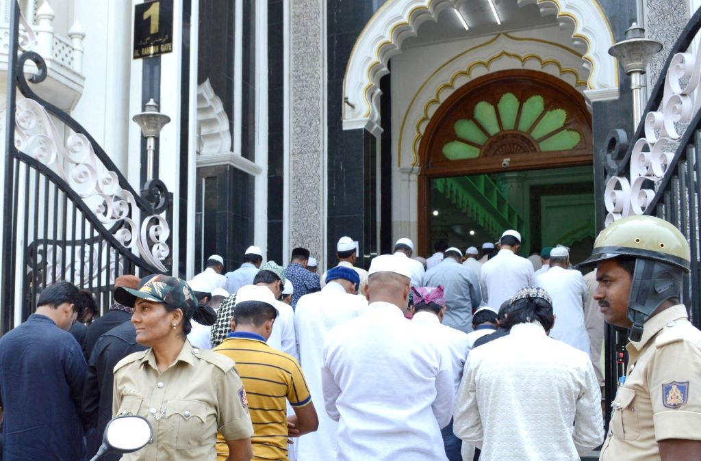 Police personnel stand guard as devotees offer prayers on the first Friday of Ramadan, at Jamia Masjid in Bengaluru on May 10, 2019.
