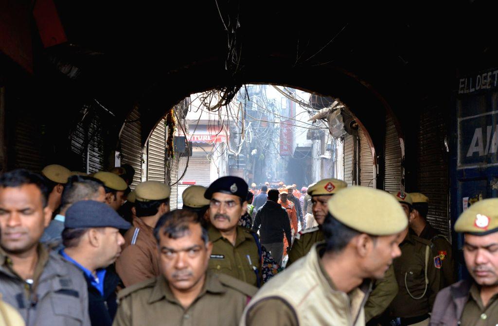 Police personnel stand guard outside the factory area in the Anaj Mandi area of Delhi's Rani Jhansi Road area where fire broke out, in Delhi on Dec 8, 2019. Reportedly 43 people were ...