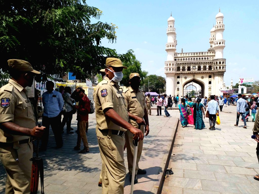 Police personnel stand guard wearing masks near the Mecca Masjid where devotees arrives to offer Friday prayers amid COVID-19 (coronavirus) pandemic, in Hyderabad on March 20, 2020.