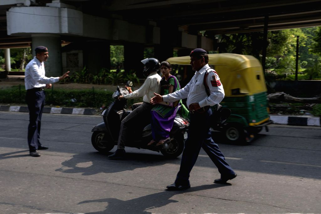 Police personnel stop a scooterist as the woman sitting behind him is not wearing helmet in New Delhi on Sept 10, 2014. Last month the Delhi government has issued a notification making wearing of ...