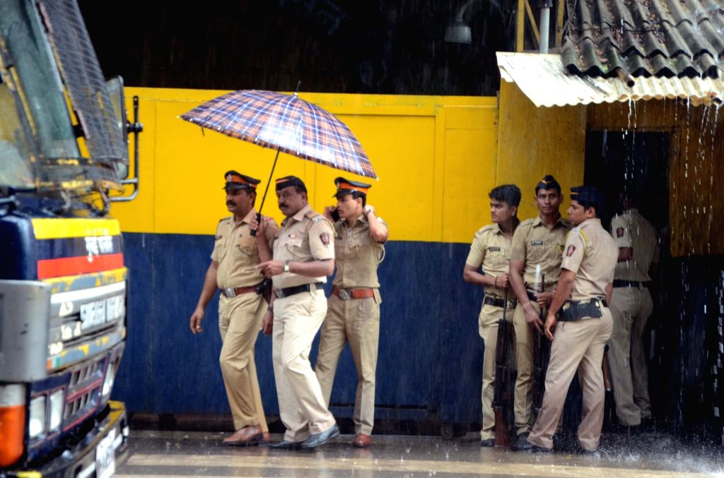 Police personnel use umbrellas to protect themselves from rains in Mumbai on June 19, 2017.