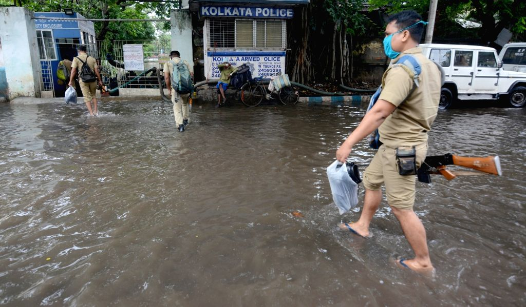 Police personnel waded through a water-logged street during rainfall in Kolkata on Friday 18 June, 2021.