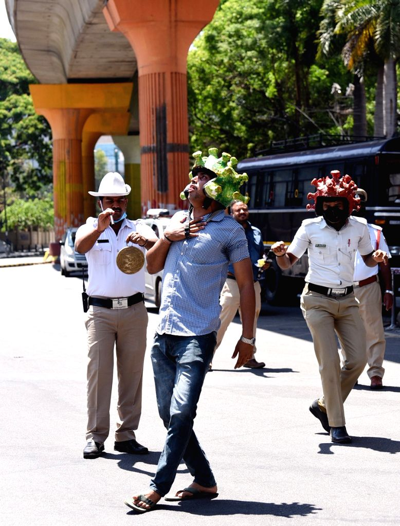 Police personnel wear 'Corona Helmets' to dissuade people from flouting the curfew during the 21-day nationwide lockdown imposed as a precautionary measure to contain the spread of ...