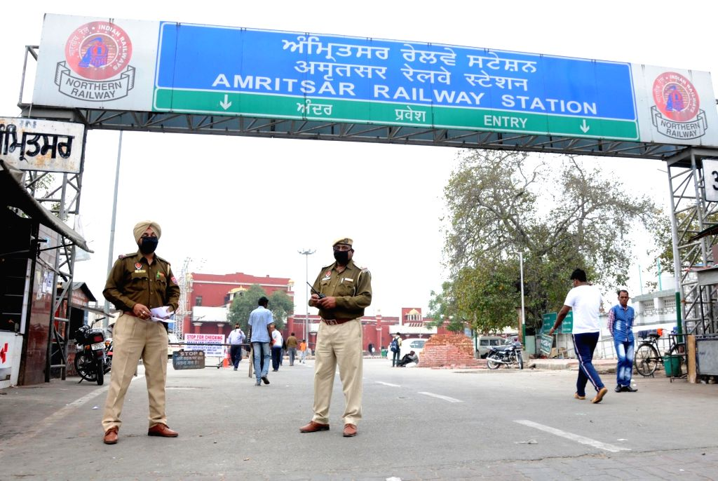 Police personnel wearing masks stand guard outside the Amritsar Railway Station, on March 21, 2020.