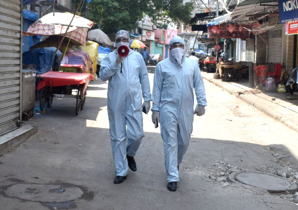 Police personnel wearing Personal Protective Equipment (PPE) suits make announcements instructing people to stay indoors in Delhi's Sadar Bazaar during the extended nationwide lockdown ...