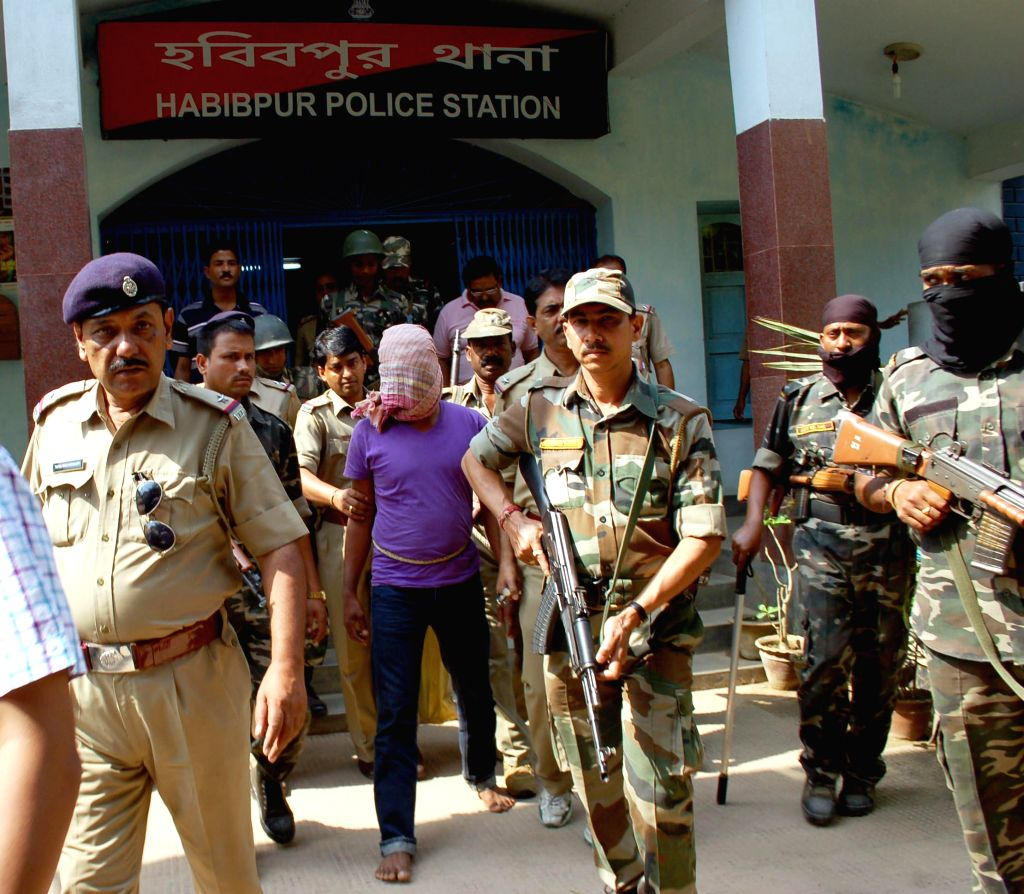 Police personnel with suspected Kamtapur Liberation Organisation (KLO) leader Malkhan Singh who was arrested from Jamalpur forest under Habibpur Police Station, at the police station in Malda ... - Malkhan Singh