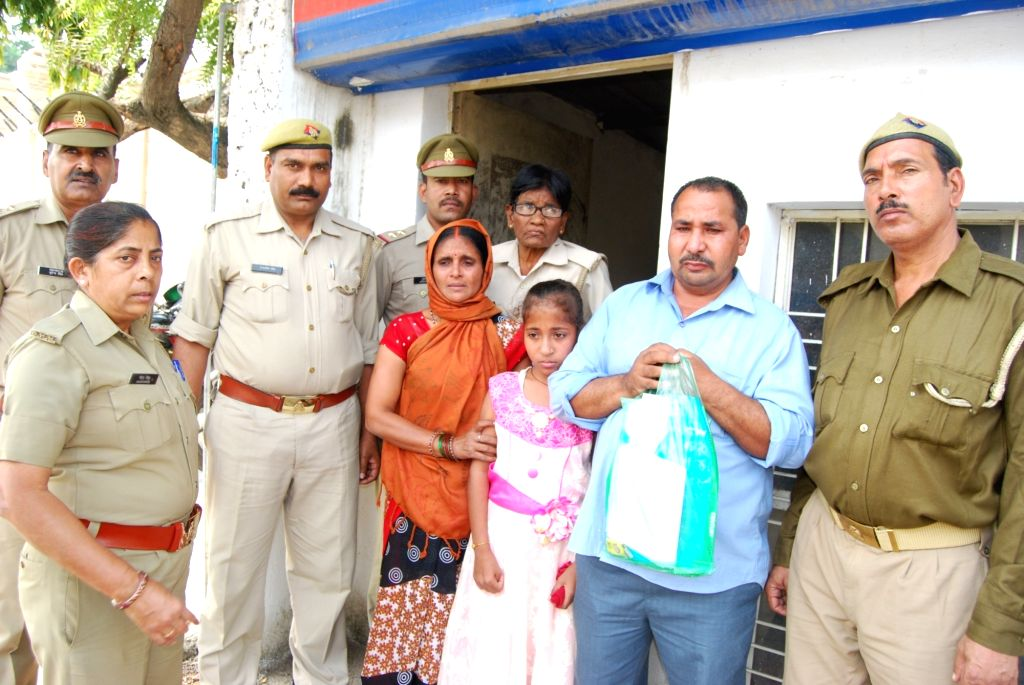 Police personnel with the parents of a 14-year-old girl, who they alleged had been kidnapped about five months ago; in Lucknow on Oct 25, 2018. The parents tried to set themselves on fire ...