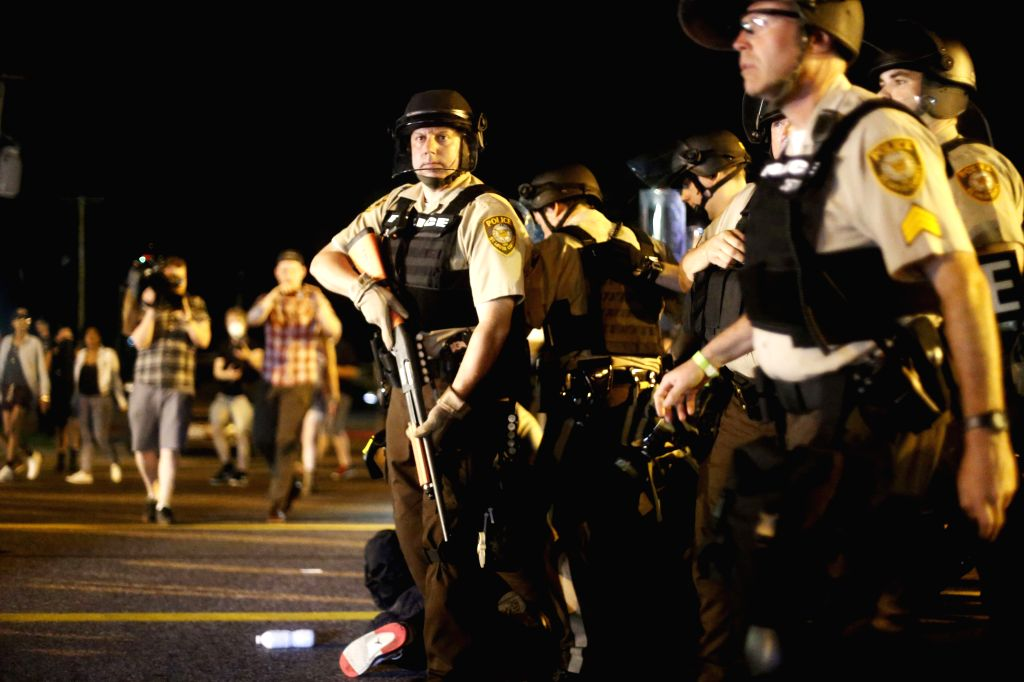 Police surround and arrest protesters on a street in Ferguson, Missouri, the United States, on August 10, 2015. A state of emergency has been declared for the city ...