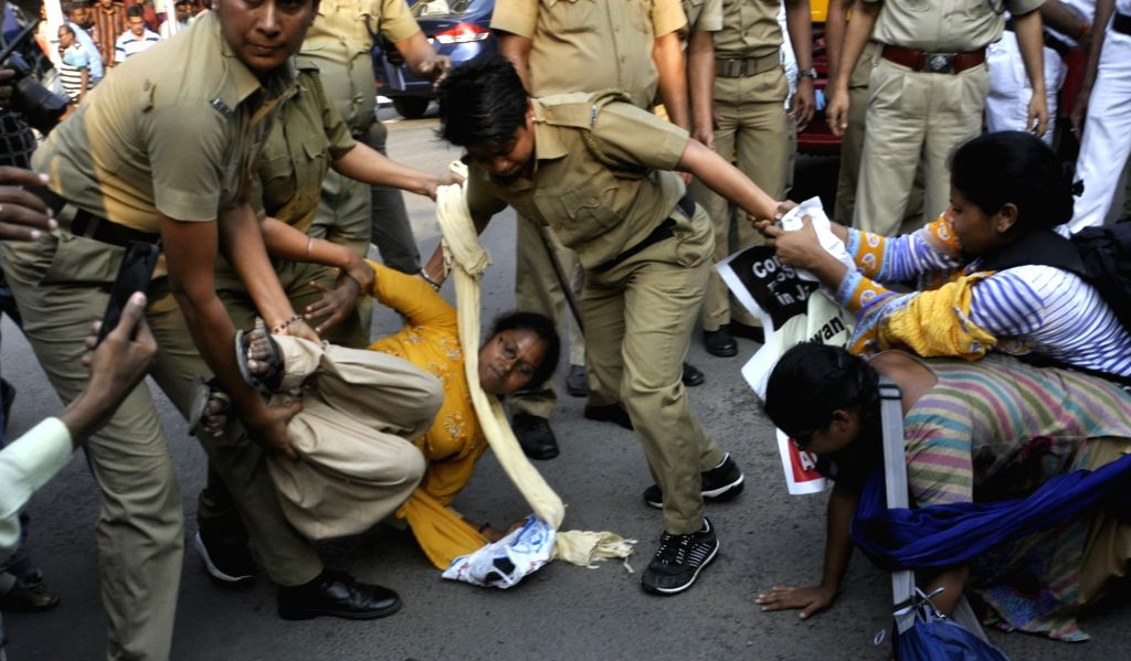 Police take away an AIDSO activist protesting against the Central and the West Bengal Government in front of Raj Bhawan in Kolkata on April 13, 2018.