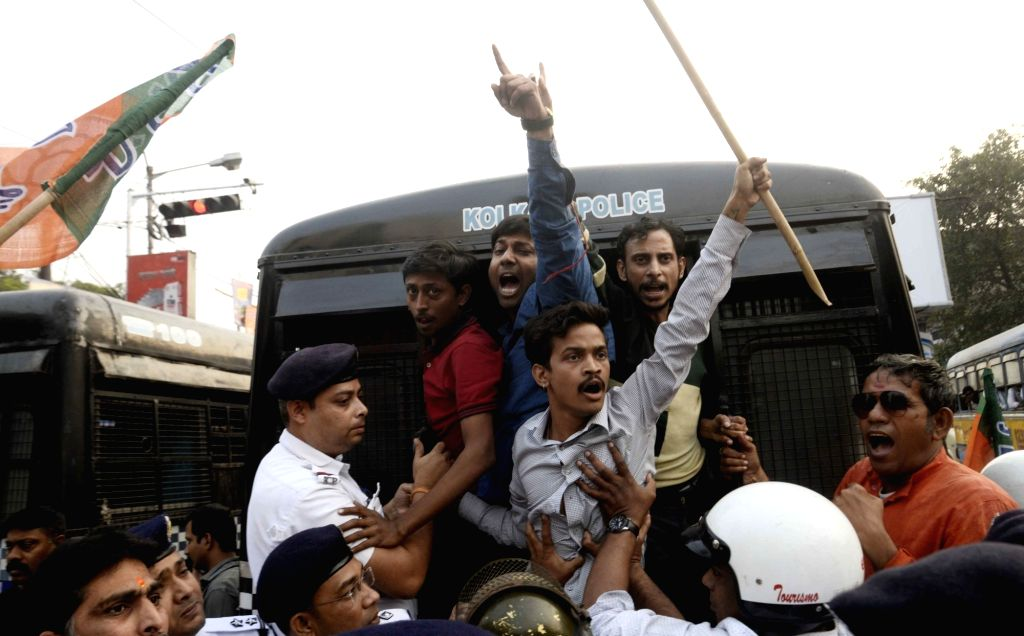 Police takes away BJP workers agitating against an attack on West Bengal (WB) BJP president Dilip Ghosh's vehicle, in Kolkata on Dec 7, 2018. Ghosh's vehicle was attacked by miscreants on ... - Dilip Ghosh