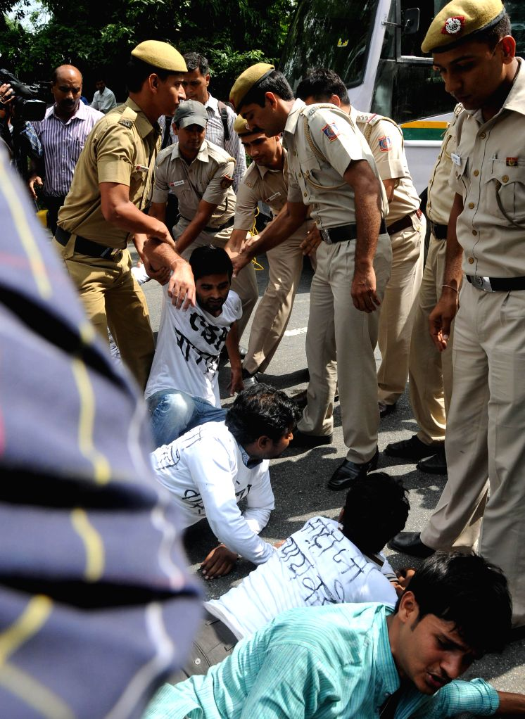 Police takes away civil service aspirants demonstrating to press for scrapping of Civil Services Aptitude Test (CSAT) in New Delhi on Aug 7, 2014.