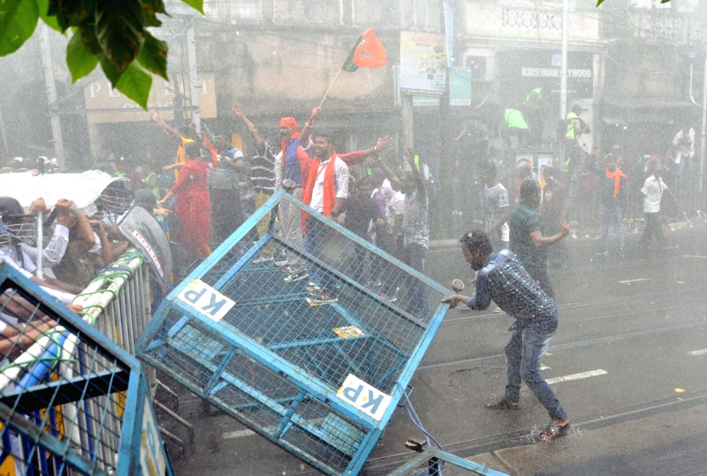 Police uses water cannons to disperse BJP activists staging a protest march against the killing of its party men in West Bengal, from Lalbazar to Kolkata Police Headquarters on June 12, 2019.